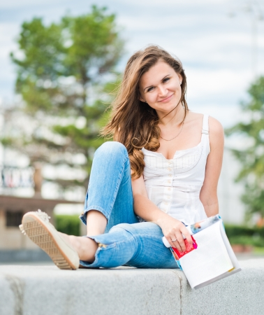 Outdoor portrait of young woman with fashion magazine  photo
