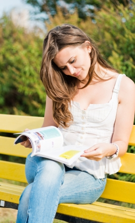 Woman read a magazine in park Stock Photo - 15832631