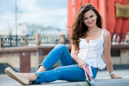 Outdoor portrait of young woman with fashion magazine  Stock Photo - 15832627