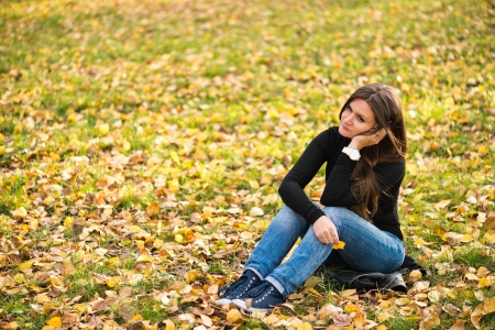 beautiful thoughtful girl  in autumn park photo