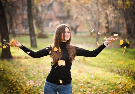 brunett: young woman throwing leaves woman in the forest