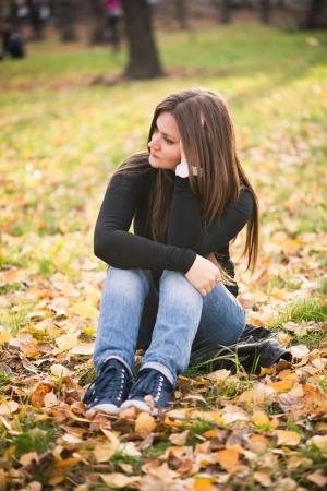 bella ragazza riflessivo in autunno parco