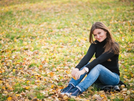 women in jeans: young woman sits on leaves in autumn park