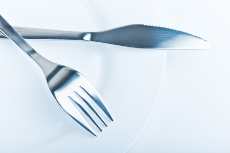 knife and fork on white plate Stock Photo - 17344744