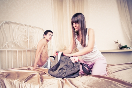 Young couple in quarrel. The girl collects things  photo