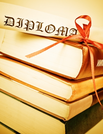 baccalaureate: Diploma with red ribbon and books