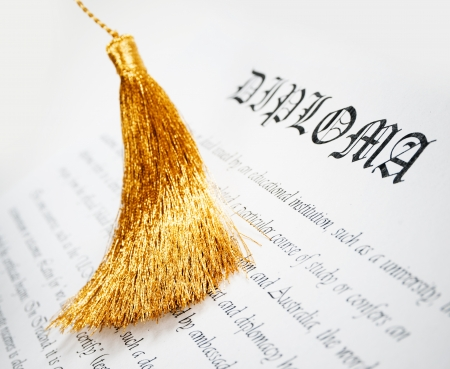 diploma with golden tassel from Graduation hat Stock Photo