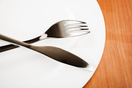 knife and fork on white plate Stock Photo - 18670255