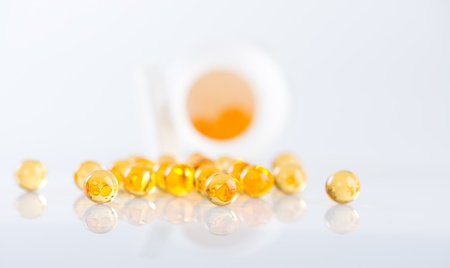 Capsules of fish oil spilled out open container Stock Photo - 18670136