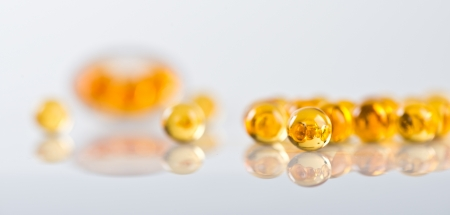 Capsules of fish oil spilled out open container Stock Photo - 18670089