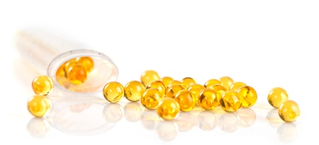Capsules of fish oil spilled out open container Stock Photo - 18670177
