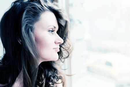 attractive young adult looking at the window with serious look  photo