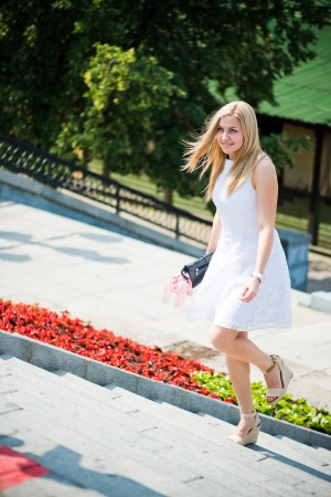 upstairs: Beautiful young blond woman in a white dress walking upstairs outdoors Stock Photo
