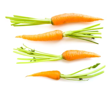 fresh carrots with leaves on white  photo