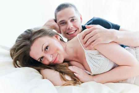 Lovely couple hugging on their bed at home  photo