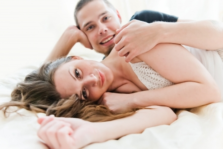 sexuality: Encantadora pareja abrazando en su cama en su casa