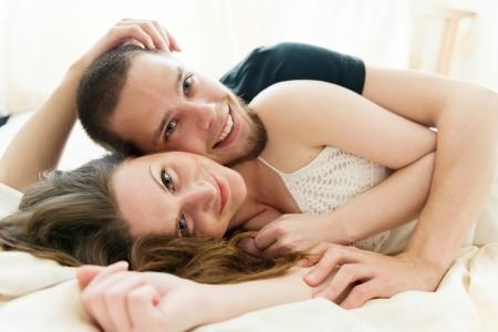 sexuality: Encantadora pareja abraz?ose en su cama en casa