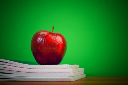 teaching material: apple on writing-books. school concept Stock Photo