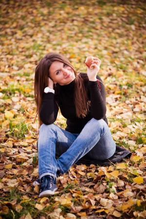 Portrait of beautiful young woman with apple in autumn park photo