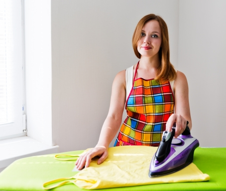 Happy young beautiful woman ironing clothes. Housework Stock Photo - 22556957
