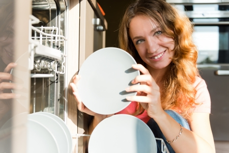 Housework: young woman putting dishes in the dishwasher  photo