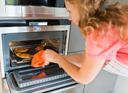 beautiful woman putting meat into oven  photo