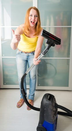 Woman cleaning the house with the Vacuum Cleaner  photo