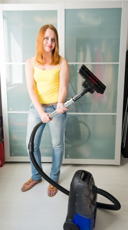 charlady: Woman cleaning the house with the Vacuum Cleaner