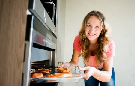 beautiful woman putting meat into oven Stock Photo - 23123620