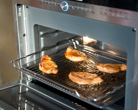 cook griddle: the meat is cooked in the oven Stock Photo