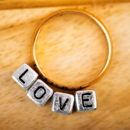 Message love spelled in matallic blocks and golden ring Stock Photo
