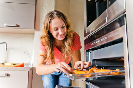 beautiful woman putting meat into oven  Stock Photo - 25805130