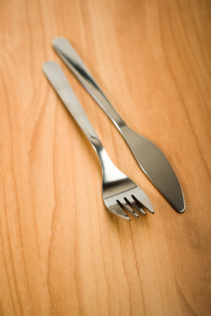 Knife and fork on wooden table  photo