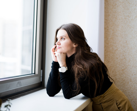 attractive young adult looking at the window  photo