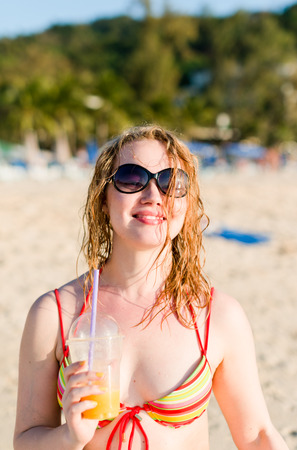 young woman with fruit cocktail relaxing on beach  photo