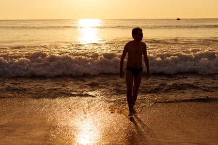 Silhouette of young man on the beach at sunset.  photo