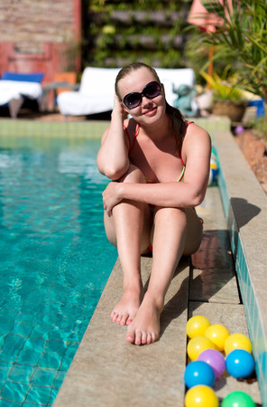 Young Happy woman sitting close to swimming pool  photo