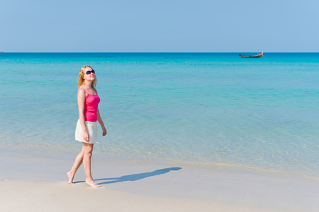 Young woman in pink top and beige skirt walking on beach  photo