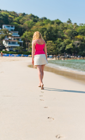 hot of footprints with woman walks on the tropical beach. Focus on footprints photo