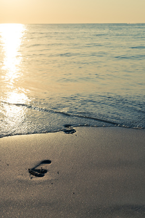 sand beach, wave and footsteps at sunset time  photo