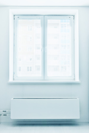 White plastic double door window with radiator under it. Domestic room.  photo