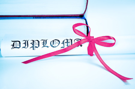 Diploma with red ribbon and books  photo