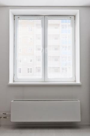 White plastic double door window with radiator under it. Domestic room. Stock Photo - 27039603