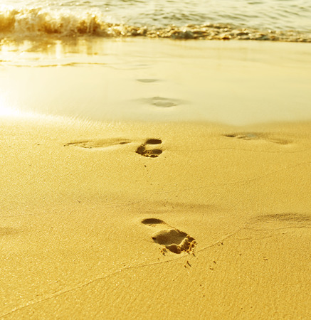 Footprint on sand with waves photo