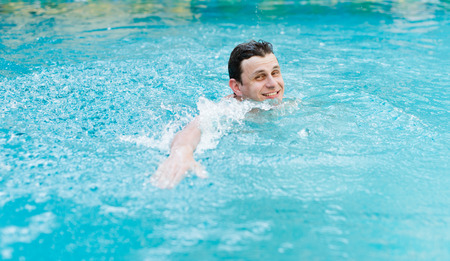 Young man swimming in pool  photo