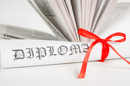 baccalaureate: Diploma with red ribbon and open book