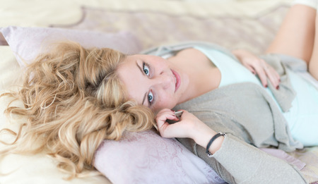 Natural cheerful blonde lying on bed and phoning in bright bedroom  photo