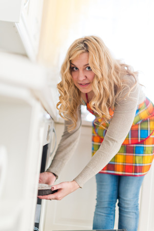 cross hatch: Woman pulling pie from oven  Stock Photo