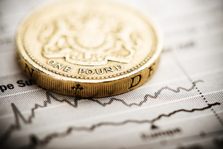 pound: One pound coin on fluctuating graph. Rate of the pound sterling (shallow DOF)