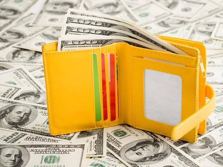 yellow Wallet Resting Upon Many United States One Hundred Dollar Notes.  photo